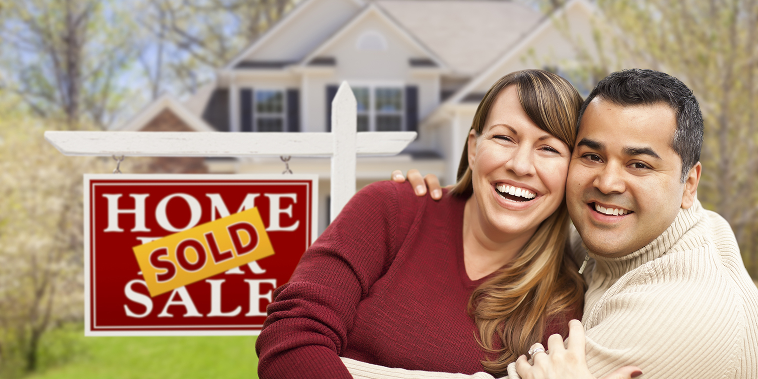 Happy Mixed Race Couple in Front of Sold Home For Sale Real Esta