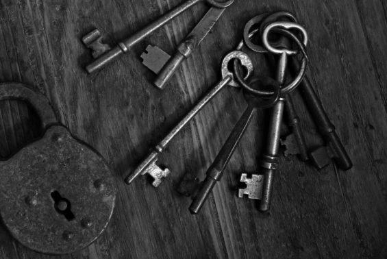 Black and white image of antique skeleton keys and padlock on da